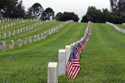 photo of line of tombstones with American Flags at each one