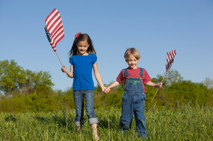 photo of a little girl and little boy holding American flags