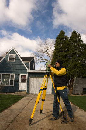 photo of a surveyor in front of a house